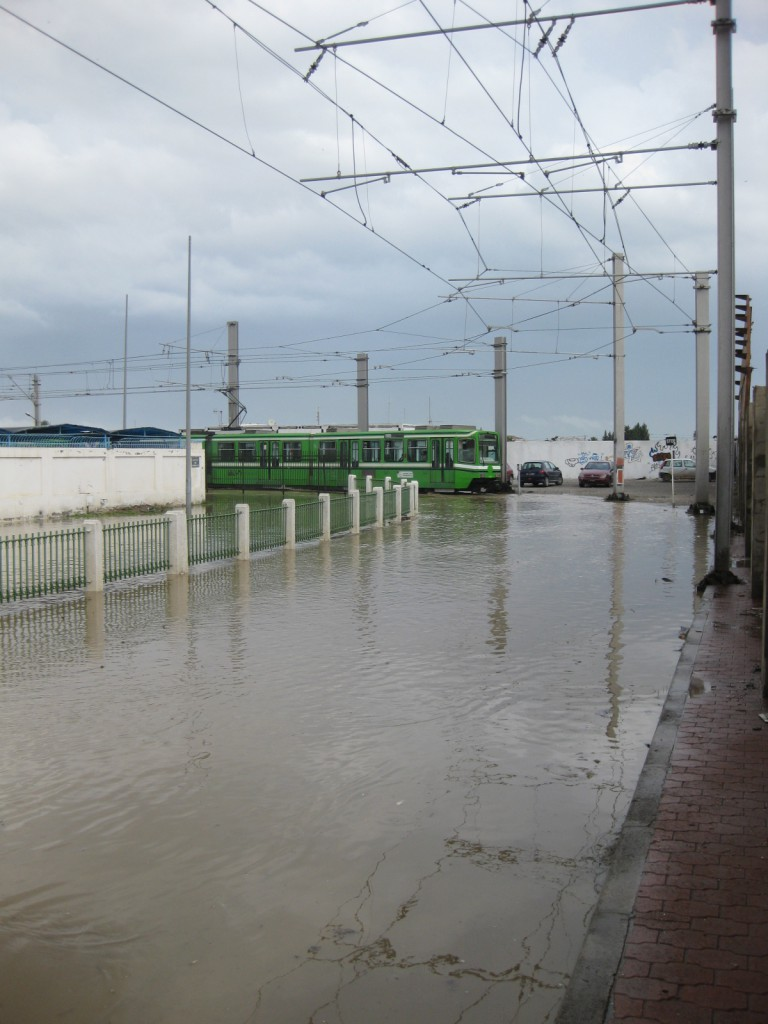 Tram departing from Tunis Marine station. The kerb on the right is the only way of passing this flooded section. The station is around the corner to the left of view